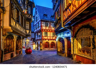 Traditional colorful half-timber houses in Colmar Old Town, Alsace, France, decorated and illuminated for Christmas