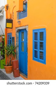 Traditional colorful house with blue windows on the street in Santorini, Fira, Greece.