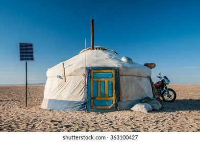 A traditional colorful Mongolian yurt with the solar panels standing in the desert under clear blue sky