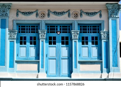 Traditional colorful Singapore Straits Chinese or Peranakan shop house with arched windows and antique blue wooden  shutters in historic Geylang