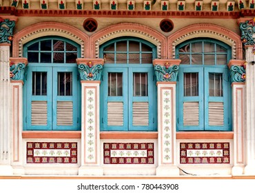 Traditional colorful Singapore Straits Chinese or Peranakan shop house with arched windows and antique blue wooden  shutters in historic Little India