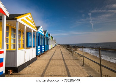 traditional colourful beach huts lining the beach promenade in the seaside town of southwold, suffolk, uk