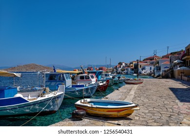 Traditional colourful Greek fishing boat mooring in secluded sea bay on Chalki island, Greece.