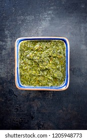 Traditional Columbian chimichurri sauce aji criollo with chili, coriander and garlic as top view in a bowl with copy space
