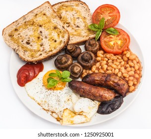 A traditional cooked full English fry-up on a plate isolated on a white background.