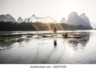 traditional cormorant fisherman throwing a net on Li river near Xingping, Guangxi province, China.