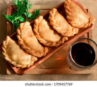 Traditional cornish pasties decorated with parsley, and a glass of wine; cenital view with a wooden background.
