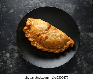 Traditional Cornish pasty filled with beef meat, potato and vegetables on black plate