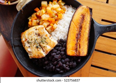Traditional Costa Rican Casado meal with rice, beans, plantains and fish