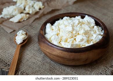 Traditional cottage cheese protein diary product, healthy breakfast in rustic wooden dish on rustic kitchen table background. Dark food photo, rustic style and natural light