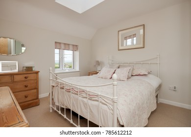 Traditional cottage style bedroom modestly dressed with floral pattern bedspread, painted wrought iron style bedstead, pine furniture, mirrors and countryside view through the small window