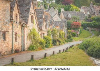 Traditional country cottages along Arlington Row in the quaint, historic English village of Bibury, Gloucestershire in the Cotswolds, UK.