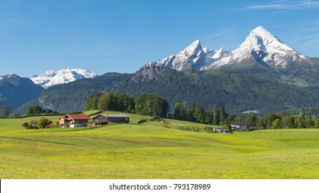 Traditional countryside Alpine spring panoramic landscape in Bavarian municipality Berchtesgaden with Watzmann mount and flowering meadow