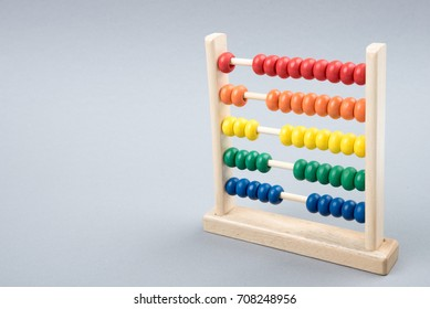 Traditional counts/abacus with colorful wooden beads on gray background. Toy abacus to learn counting. Colorful children counting frame for kids. Counts show: one, two, three, four, five. Copy space.