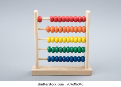Traditional counts/abacus with colorful wooden beads on gray background. Toy abacus to learn counting. Colorful children counting frame for kids. Counts show: one. Copy space. Top view.