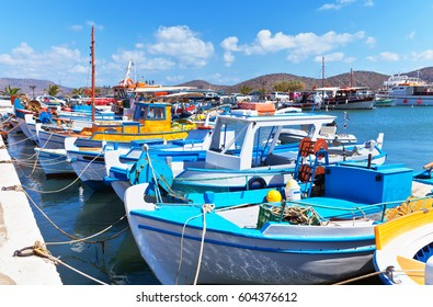 Traditional Cretan fishing boats on the quay of the port town of Elounda on a summer sunny day. Crete, Greece