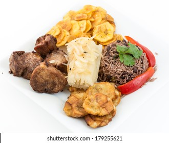 Traditional Cuban Cuisine. Fried pork, yukka or cassava boiled and with a mojo, congri rice plus salty green banana fries or chips.