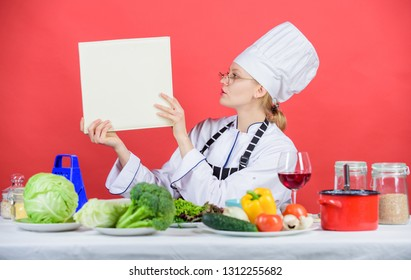 Traditional cuisine. Culinary expert. Woman chef cooking healthy food. Girl read book top best culinary recipes. Culinary school concept. Female in hat and apron knows everything about culinary arts.