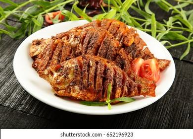 Traditional cuisine from India-Fried fish with spices and herbs on a wooden background.
