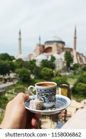 Traditional cup of  turkish coffee in hand with a mosque Ayasofya background. Travel to Istanbul, Turkey. Soft focus and beautiful bokeh. Travel and romantic concept.