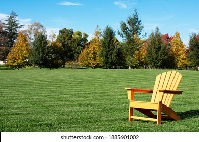 Traditional curveback sunset plastic outdoor patio adirondack chair with contoured backs and seats on green grass of empty manicured lawn surrounded by autumn trees