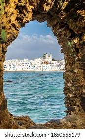 Traditional Cycladitic view of whitewashed houses with the christian church framed with a stone arch   in Naousa  Paros island, Greece