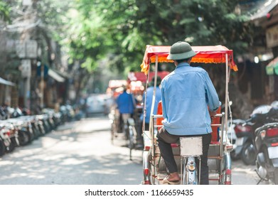 Traditional cyclo ride down the streets of Hanoi, Vietnam. The cyclo is a three-wheel bicycle taxi that appeared in Vietnam during the French colonial period.
