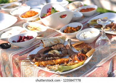 Traditional Cypriot meze and mix meat and chicken shish, adana, lamb chops, wings, seftali kebab table with charcoal barbecue in the garden for self cooking during the eating time