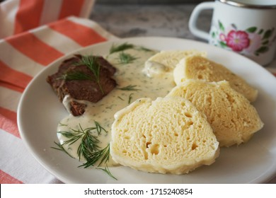 Traditional czech food: Creamy dill sauce (koprovka) with yeast dough dumplings (knedliky) and boiled beef - Shutterstock ID 1715240854