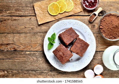 Traditional Czech gingerbread cakes, dried pieces of lemon, cacao powder, milk and raspberry jam on white plate. View from above.