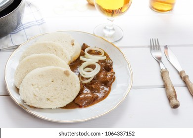 Traditional czech goulash with dumplings and beer on white table