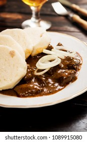 Traditional czech goulash with dumplings and beer on dark table