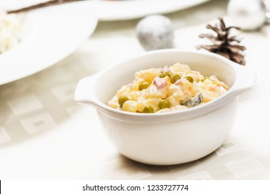 Traditional czech potato salad with mayonnaise and vegetables in white plate