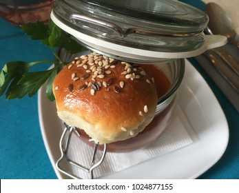 Traditional Czech soup in a glass jar with a small roll topped with sesame seeds on top balancing on the of the bowl in a restaurant in Prague. Traditional Czech cuisine of soup on turquoise cloth.