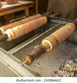 "Traditional Czech sweet treat ""Trdelnik"". To prepare on a special wooden skewers over hot coals. A popular dish among tourists. street food of Prague."