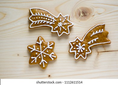 Traditional Czech tasty white painted brown gingerbreads, Christmas comets and stars on wooden table, simplicity still life
