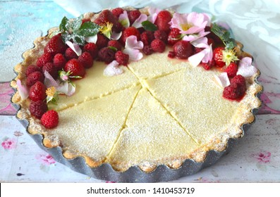 Traditional czech tvaroznik - quark cheese cake (cream cheese cheesecake made with custard cheese or tvaroh), with raisins and topeed with berries and flowers (wild roses), with flaky butter crust