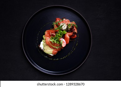 traditional Danish open sandwich smorrebrod with salmon toast for breakfast or lunch with rye bread, sliced avocado and mozzarella, healthy and delicious snack, chef making food