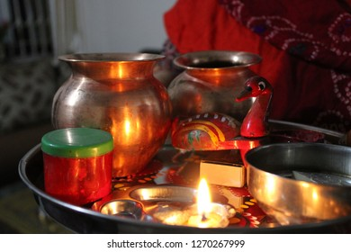 Traditional decorative indian plate for offering prayers to god on festivals. It contains water in copper jugs, a deepak with red kumkum for tilak.