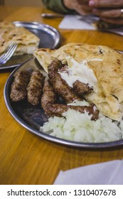 Traditional delicious Bosnian Cevapi in Bascarsija, Sarajevo, served on metal plates with onions and lepinja bread. Traditional cevapcici serving.