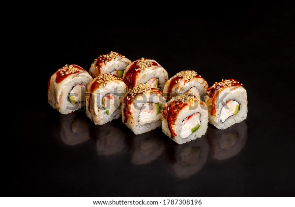Traditional delicious fresh sushi roll set on a black background with reflection.  Sushi roll with rice, cream cheese, unagi, salmon, sesame. Philadelphia. Sushi menu. Japanese kitchen, restaurant.
