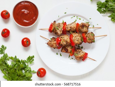 Traditional delicious turkey or chicken shish kebab skewer barbecue meat with tomatoes, pepper and sauce. Served on white kitchen table background. Natural light. Picnic bbq gourmet.