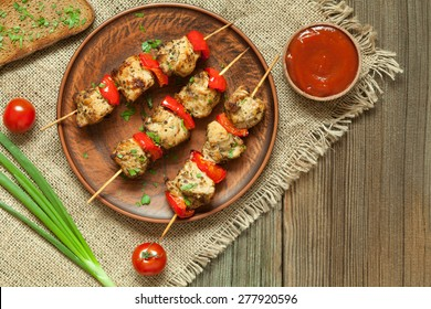 Traditional delicious turkey kebab skewer barbecue meat with tomatoes and sauce on clay dish.  Served on kitchen table background. Rustic style, natural light. Picnic bbq gourmet.