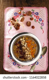 traditional dessert, ashura in a copper plate, pink embroidered small table cloth, spoon, nuts, top view, ashure, noah's pudding, asure