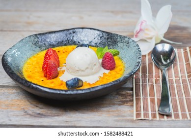 Traditional dessert cream catalana and creme brulee in a beautiful plate on a wooden table in a restaurant or cafe. Sweet treat. Food and desserts with tropical decorations and flowers.
