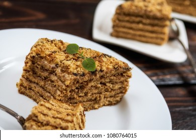 Traditional dessert honey cake with walnut and with coffee on dark wood table