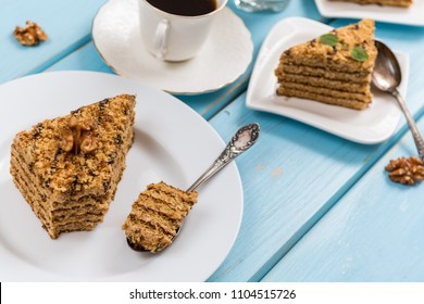 Traditional dessert honey cake with walnut and with coffee on blue wood table