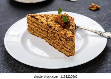 Traditional dessert honey cake with walnut and with coffee on dark stone table