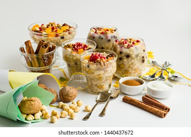 Traditional Dessert,Noah's Pudding or Asure in the glass bowls on the white surface with walnuts,cinnamon sticks,handmade lace napkin and hazelnuts.