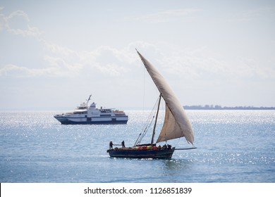 traditional dhow transportation vessel contrasted with a modern boat in the background